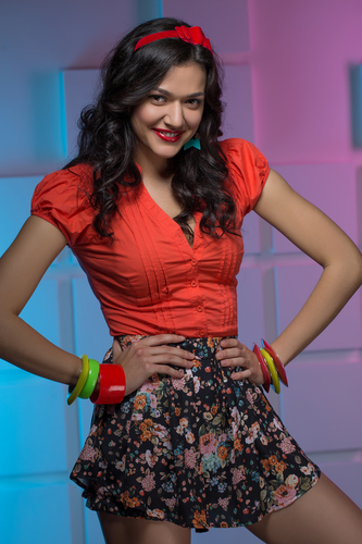 Portrait of sexy dressed in bright clothes brunette in the studi